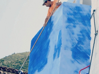 Man painting an outside wall blue in Chefchaouen