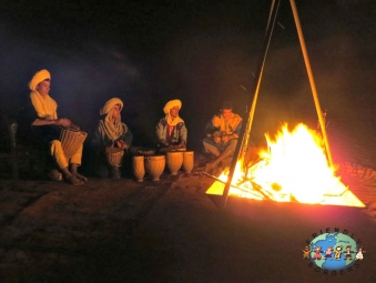 Men drumming around the campfire and singing at night