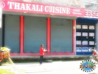 Thakali boy stands outside a restaurant in Pokhara, Nepal