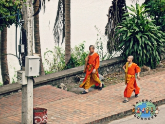 Two Buddhist monks walk down the street in Luang Prabang