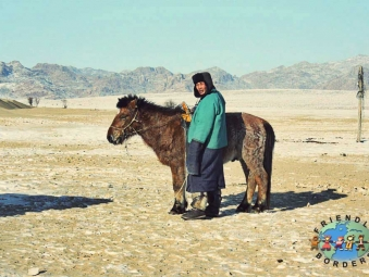 A Mongolian nomad rides his horse in Central Mongolia